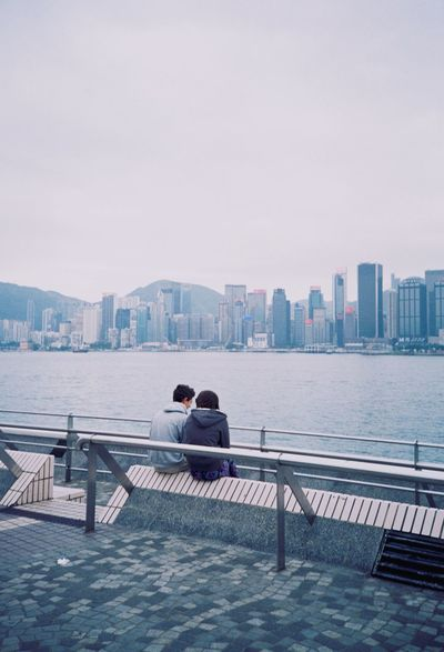 Two People Heterosexual Couple Skyscraper City Couple - Relationship Railing Togetherness Love Cityscape Architecture Building Exterior Sea Relaxation Urban Skyline