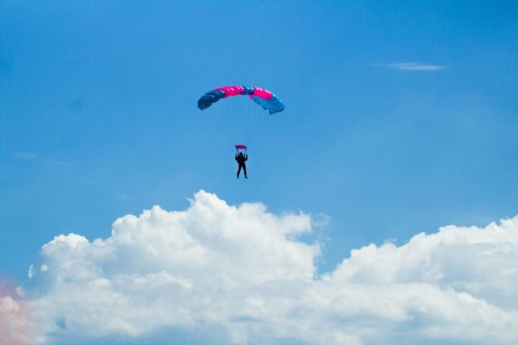 Low angle view of silhouette person paragliding against blue sky