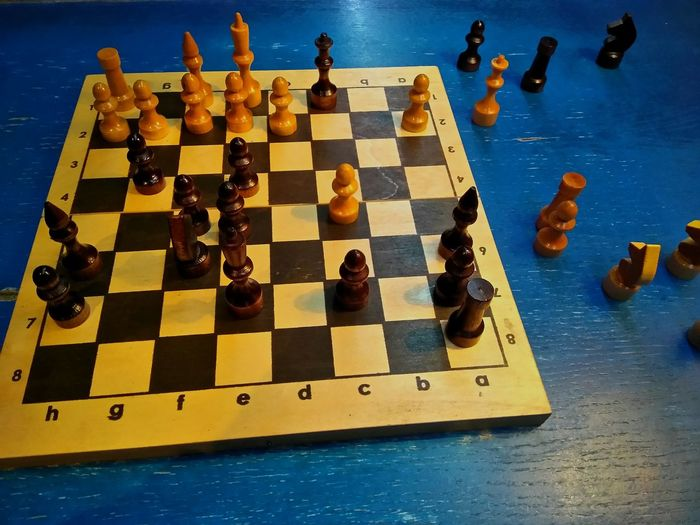 High angle view of chess board on blue table