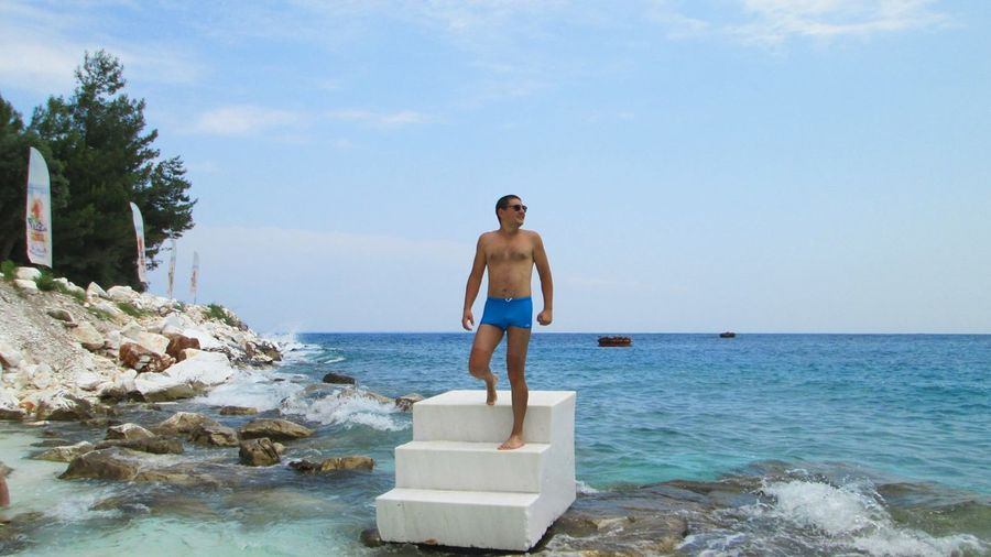 Full length of shirtless man standing on steps in sea against sky