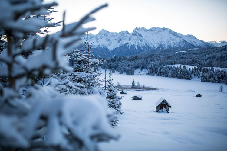 Scenic view of snow covered field and  barn with mountains against sky, bavaria, germany.
