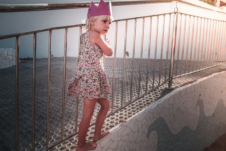 Girl standing by railing