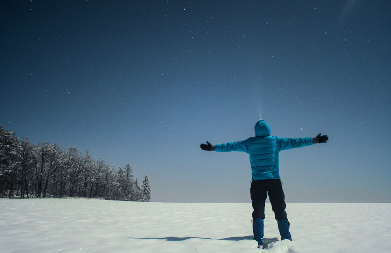Rear view of person standing on snow covered field against sky at night