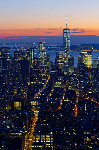 One world trade center in illuminated city against sky during sunset