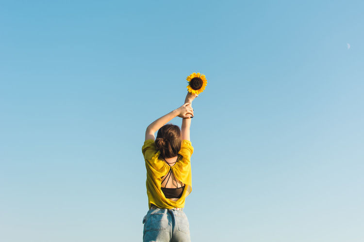 Low Angle View Of Woman Holding Sunflower Against Sky