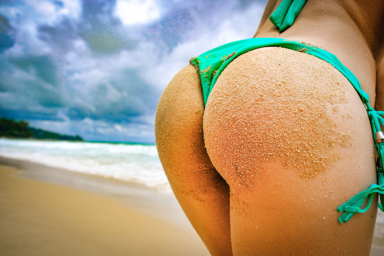 Close-up of young woman buttocks with sand at beach