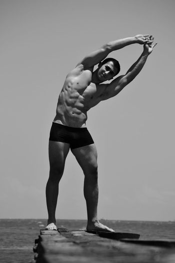 Full length portrait of bodybuilder exercising on pier over sea against clear sky