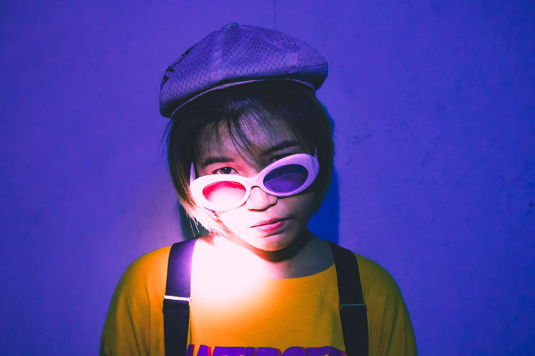 Portrait of young woman wearing sunglasses against blue wall