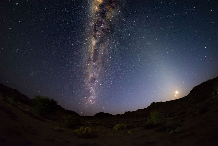 Starry sky and Milky Way arc, outstandingly bright, with rising moon, captured from the Namib desert in Namibia, Africa. The Small Magellanic Cloud on the left hand side. Astronomy Beauty In Nature Galaxy Landscape Milky Way Mountain Nature Night No People Outdoors Scenics Sky Space Star - Space Starry Tranquility