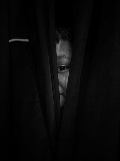 Close-up of boy looking through curtain