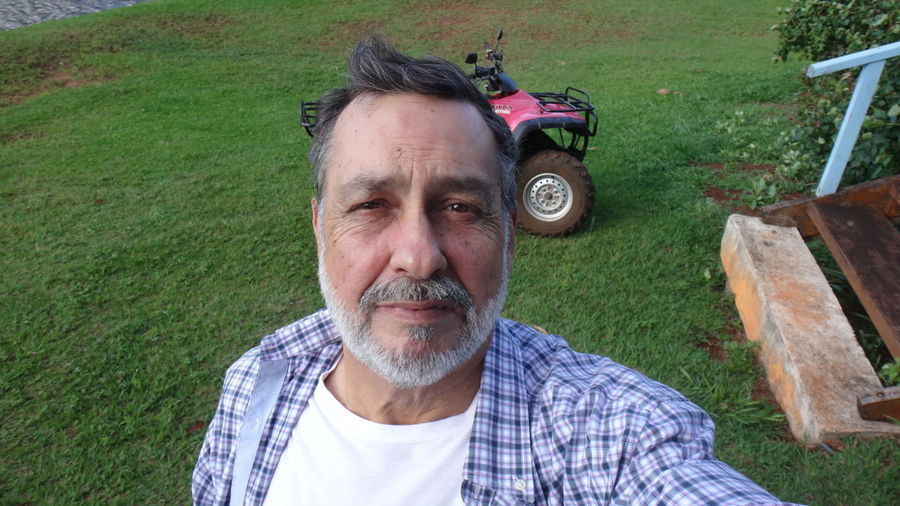 Portrait of senior man standing on grassy field against quadbike at park