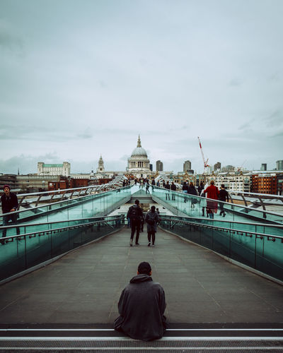 Rear view of man sitting on bridge against sky