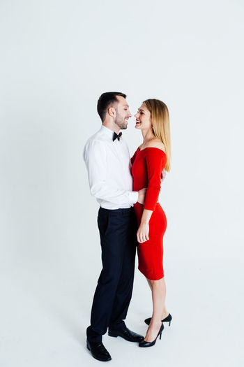 Full length side view of elegant couple standing against blue background