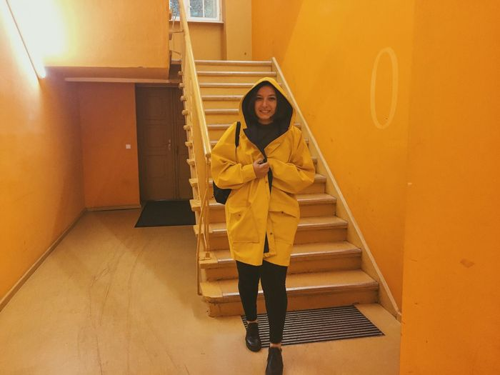 Full length portrait of woman wearing yellow raincoat by steps at home