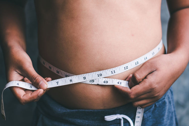 Midsection of shirtless boy measuring stomach