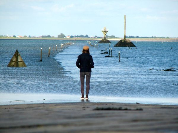 A girl in front of a periodically flooded road. Atlantic Ocean Casual Clothing Ebb Tide Falling Tide Floaded France From Behind From The Back High Tide Passage Du Gois Road Road Sign Standing Tide île De Noirmoutier The Traveler - 2018 EyeEm Awards