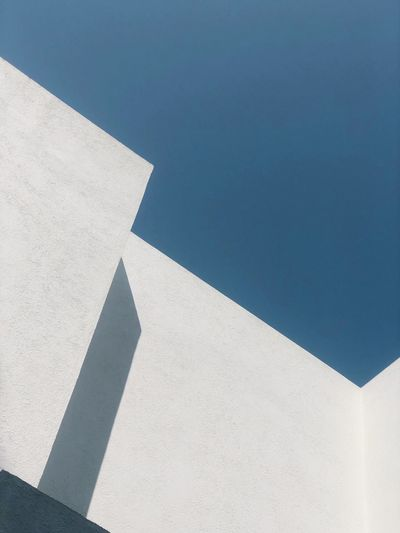 Low angle view of white wall against blue sky