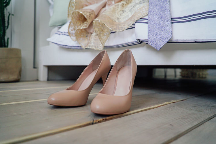 Women high heeled shoes, evening wedding dress and a man tie near the bed Low Section Shoe Human Leg Women Indoors  Adult One Person Human Body Part High Heels Body Part Real People Flooring Lifestyles Fashion Females Hardwood Floor Wood Day Sitting Human Foot Human Limb