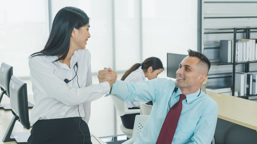 Business people shaking hands with colleague in background at office