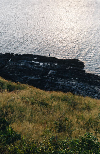 Water Sea Alone Solitude Tranquility Nature Grass Isolation Isolated Loneliness Sad Outdoors Beauty In Nature High Angle View Fisherman Rock Land