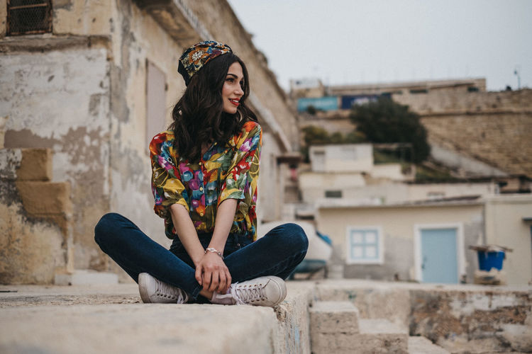 Young woman sitting against building