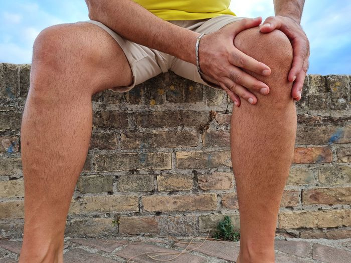 Low section of man sitting on stone wall
