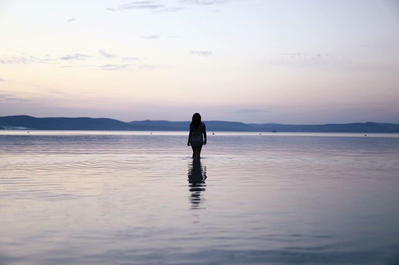 Rear view of woman standing in river against sky during sunset