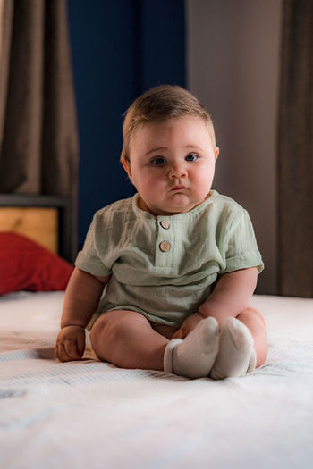 Portrait of cute baby girl sitting on bed