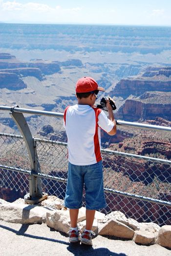 Rear view of boy filming grand canyon with video camera