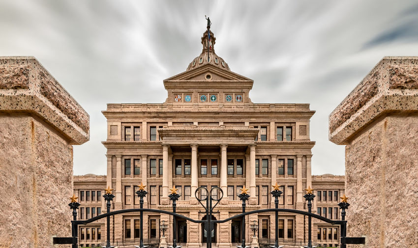 Texas State Capitol Building in Austin, with the flag of Texas Texas Capitol Austin State Building Capital Sky Day Downtown Dome Government Travel Blue Architecture City USA Landmark Monument Congress Old Historic Flag Federal Tourism Stone Cloud Statue America Law Politics United Legislature  TX Political Symbol Spring Space Green Built Structure Architectural Column Travel Destinations Outdoors Façade Building Exterior The Past History Classical Style No People