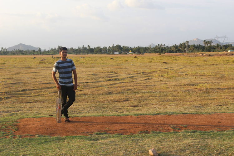 Dry lake , Cricket Pitch Cricket Pitch Cricket Field Dry Lake Beauty In Nature Casual Clothing Day Environment Field Full Length Grass Land Landscape Leisure Activity Lifestyles Nature Non-urban Scene One Person Outdoors Plant Real People Rear View Red Pitc Scenics - Nature Sky Standing