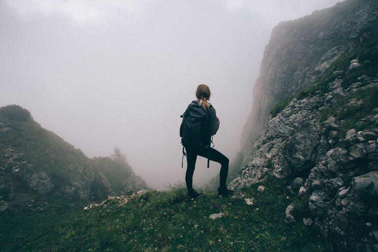 Rear view of man standing on rock against sky during foggy weather