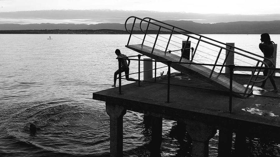 Silhouette people standing on pier by lake against sky