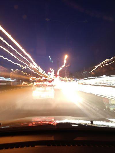 Illuminated light trails on road at night