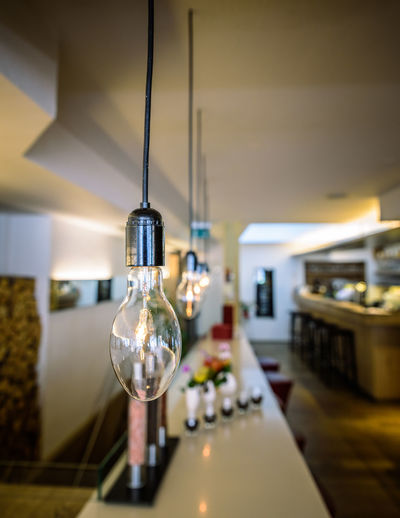Illuminated light bulbs hanging in restaurant