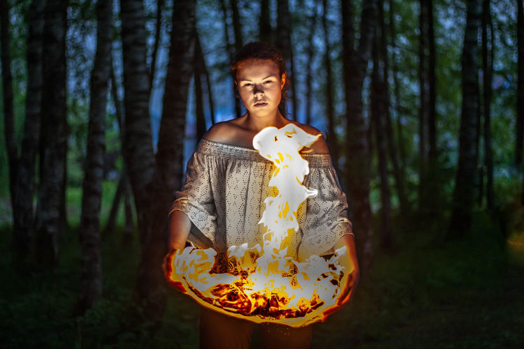 Digital composite image of woman holding fire while standing in forest