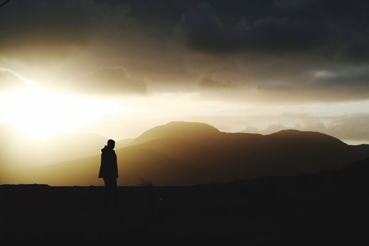 Silhouette Person Standing On Field Against Cloudy Sky During Sunset