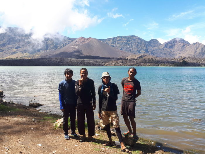 Portrait of friends standing on lake against mountains