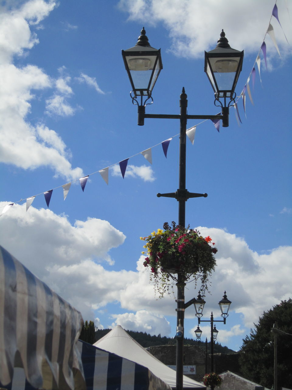 Low Angle View Of Lamp Post And Bunting Against Blue Sky