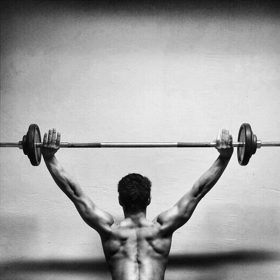 Rear View Of Shirtless Muscular Man Exercising With Barbell By Wall