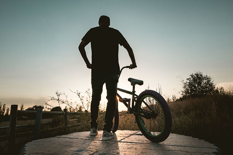 Rear view of man standing by bicycle against sky
