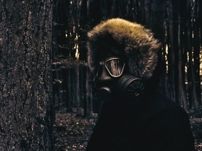 Close-up of person wearing gas mask while standing by tree in forest