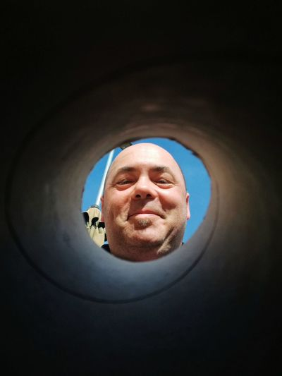Low Angle View Of Man Looking Through Hole