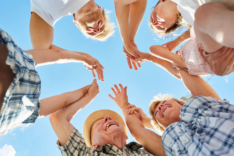 Low angle view of family with arms raised against blue sky