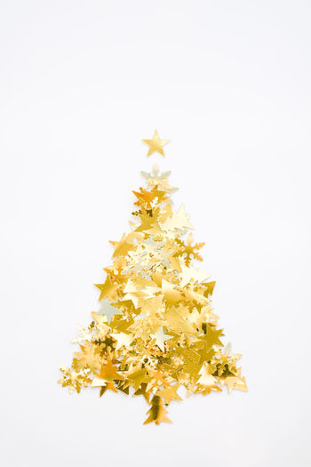 Annual Event Celebration Celebration Event Celebrations Christmas Christmas Decoration Christmas Ornament Christmas Tree Glitter & Sparkle Glittering Gold Colored Golden Happy New Year Party - Social Event Shape Star Shape White Background Christmas Tree Shape Confetti Golden Confetti