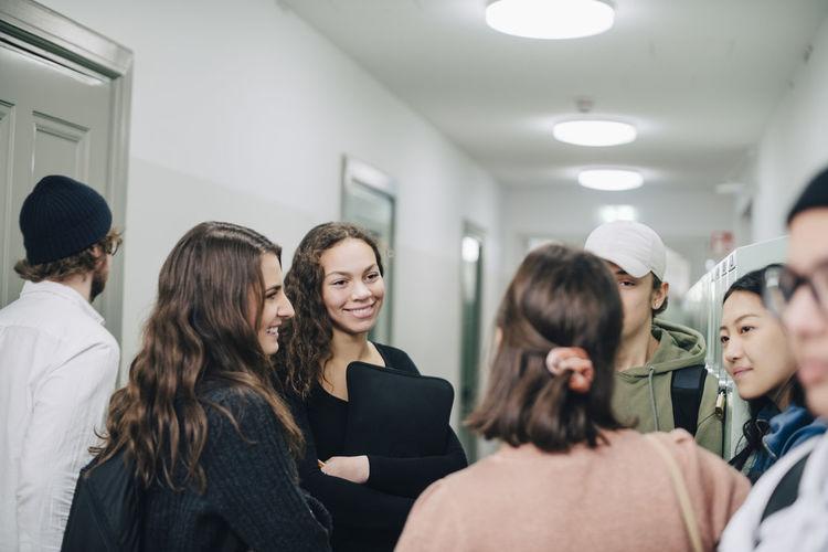 Rear view of friends standing in corridor