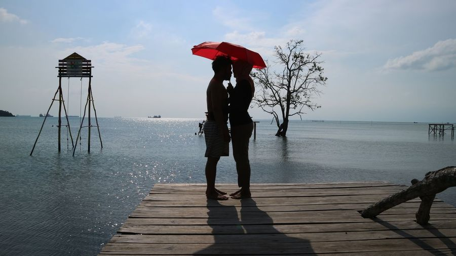 Couple holding umbrella while standing on pier over sea at beach