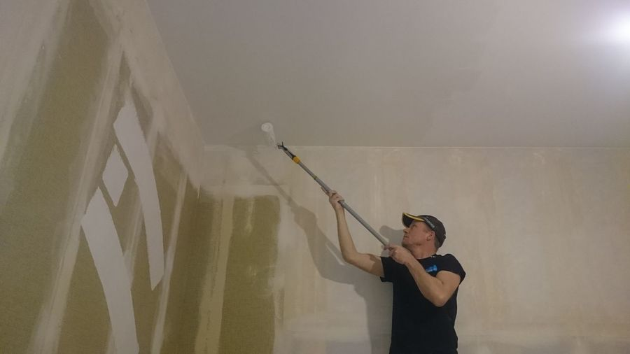 Low angle view of man painting ceiling at home