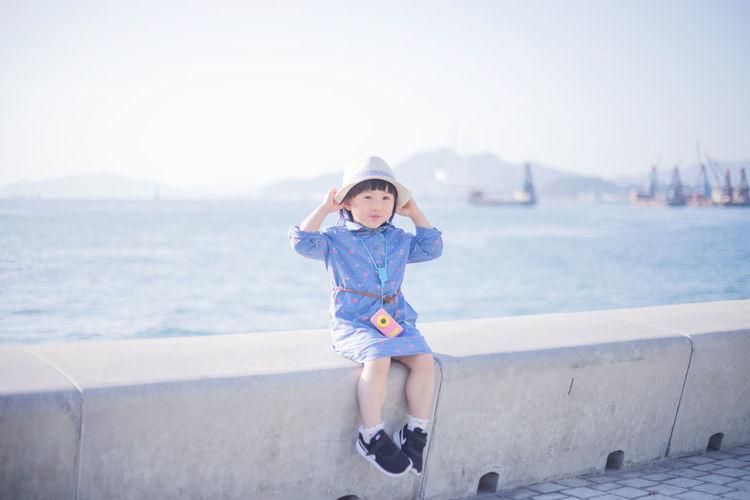 Portrait of boy in sea against sky