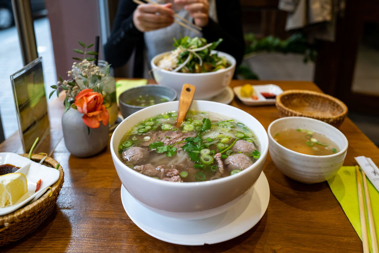 Vietnamese Food Table Bowl Food Food And Drink Freshness Healthy Eating Wellbeing Ready-to-eat Indoors  Serving Size Soup Focus On Foreground Business Vegetable Real People Restaurant Plate Spoon Wood - Material Crockery